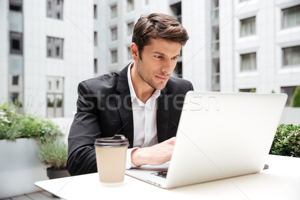 Businessman using laptop in outdoor cafe Stock photo © deandrobot