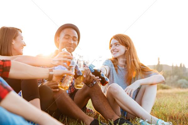 Groupe heureux jeunes amis potable bière Photo stock © deandrobot