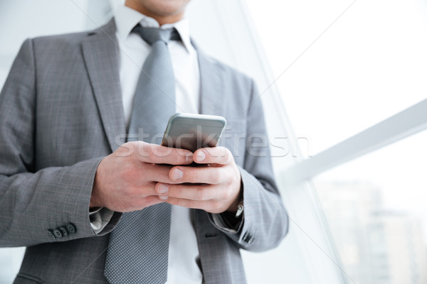 Cropped image of business man using phone near the window Stock photo © deandrobot