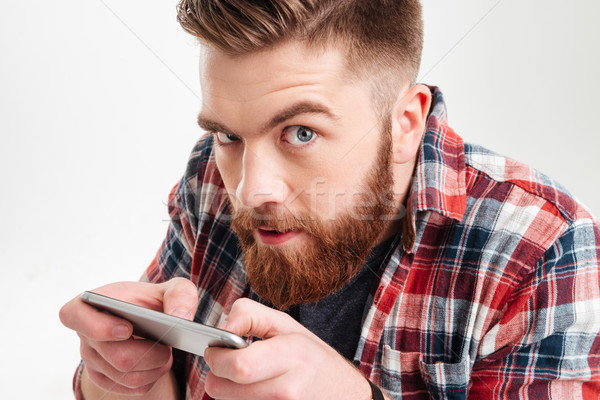 Suspicious man in shirt playing game on his smart phone Stock photo © deandrobot