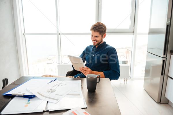 Okos fiatalember néz tabletta ül asztal Stock fotó © deandrobot