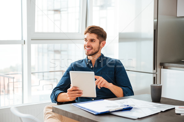 Young man in office analyzing finances with tablet Stock photo © deandrobot