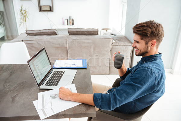 Cheerful young man drinking coffee while sitting near laptop Stock photo © deandrobot
