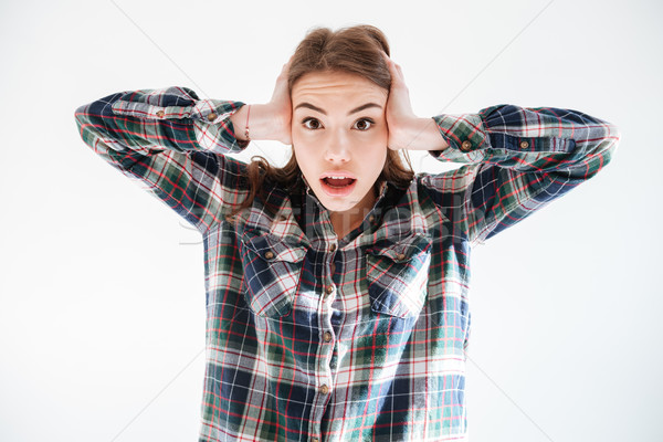 Shocked amazed young woman covered ears with hands Stock photo © deandrobot