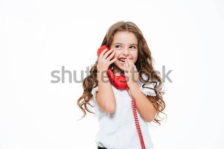Smiling shy little girl laughing and talking on red telephone Stock photo © deandrobot