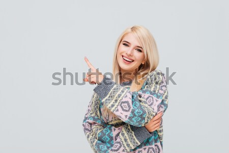 Cheerful young blonde woman in sweater pointing finger away Stock photo © deandrobot