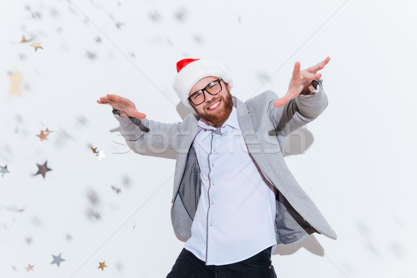Cheerful bearded man in santa claus hat smiling and dancing Stock photo © deandrobot