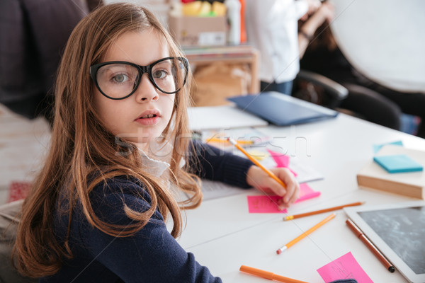 Beautiful little girl sitting and writing on colorful sticky notes Stock photo © deandrobot