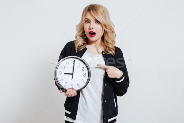 Surprised young teenager girl holding alarm clock and pointing finger Stock photo © deandrobot