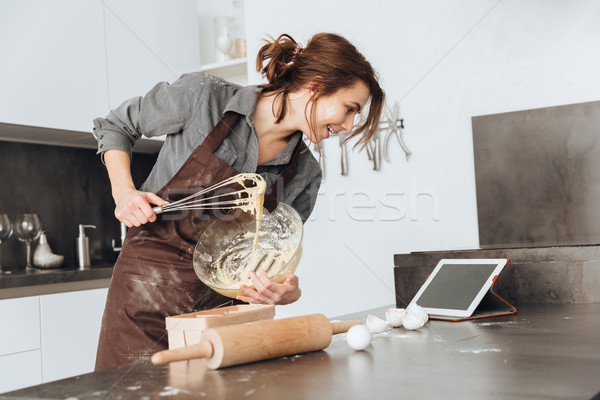 Pretty lady standing in kitchen and cooking the dough Stock photo © deandrobot