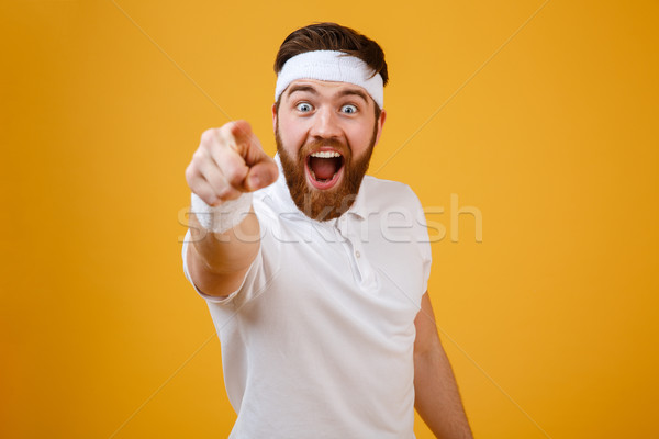 Happy bearded sportsman pointing at camera Stock photo © deandrobot