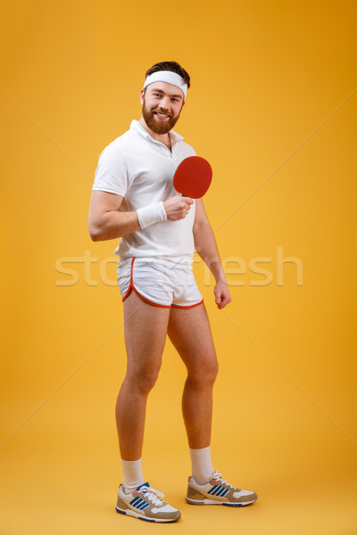 Happy young sportsman holding racket for table tennis. Stock photo © deandrobot