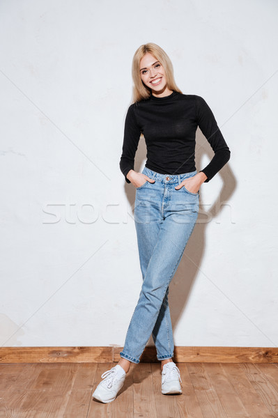 Woman standing with hands in pockets and legs crossed Stock photo © deandrobot