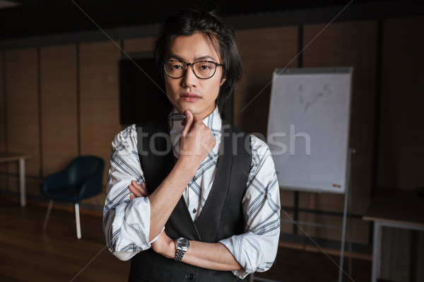 Attractive young asian man looking at camera. Coworking concept. Stock photo © deandrobot