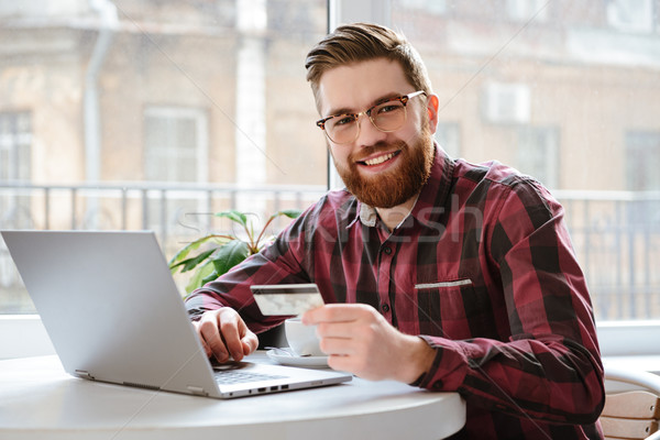 Bearded young man holding debit card. Stock photo © deandrobot