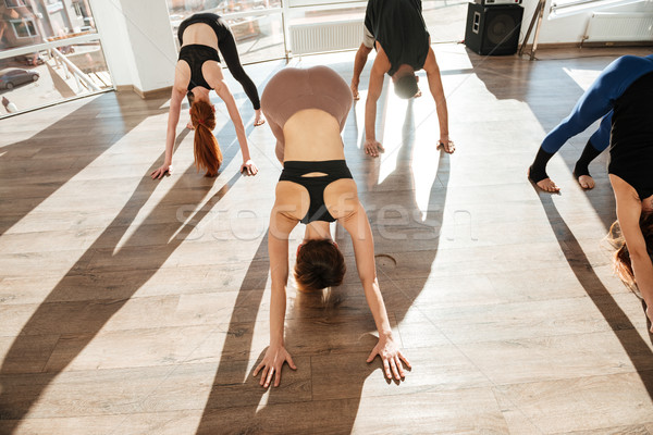 Group of people working out and practicing yoga in studio Stock photo © deandrobot