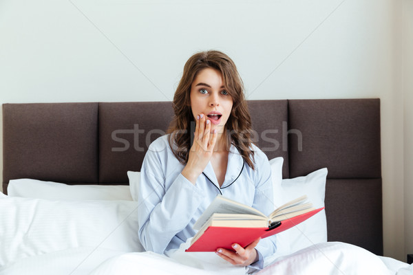 Portrait of a shocked astonished woman in pajamas holding book Stock photo © deandrobot