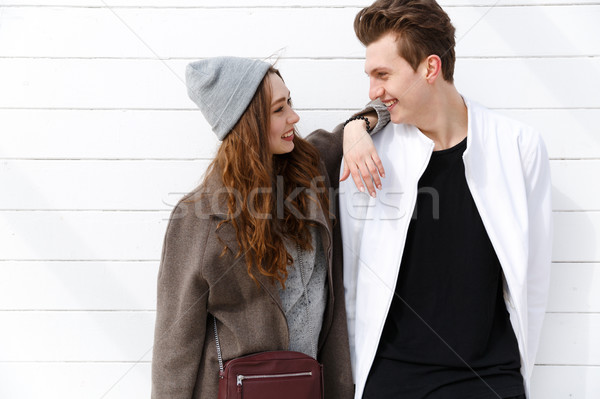 Cheerful young couple standing and looking at each other Stock photo © deandrobot