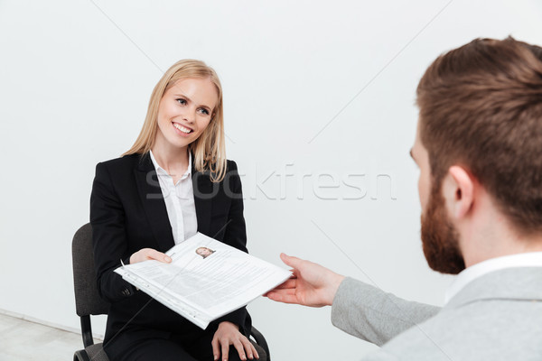 Smiling lady sitting in office near her boss holding resume Stock photo © deandrobot