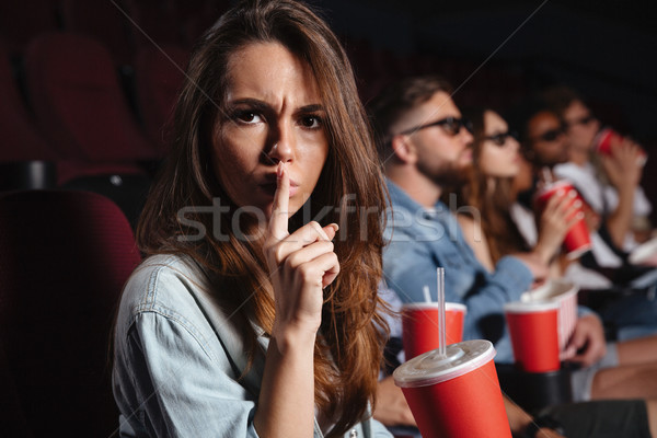 Lady sitting in cinema showing silence gesture. Stock photo © deandrobot