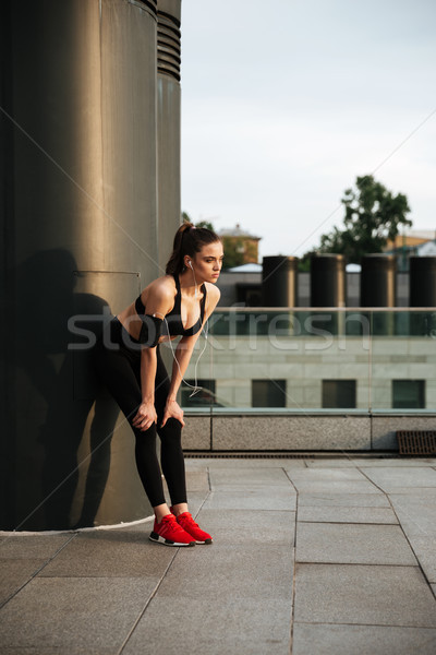 Concentrated young sports lady standing with earphones Stock photo © deandrobot