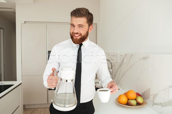 Felice barbuto uomo d'affari caffè cucina guardando Foto d'archivio © deandrobot