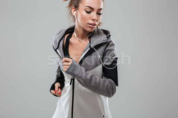 Young female runner in warm clothes running in studio Stock photo © deandrobot