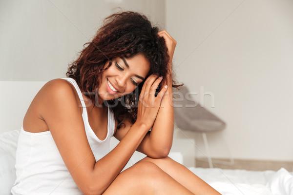 Sorridente africano mulher sessão cama manhã Foto stock © deandrobot