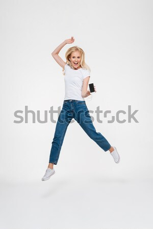 Portrait of a happy pretty girl jumping with hands raised Stock photo © deandrobot