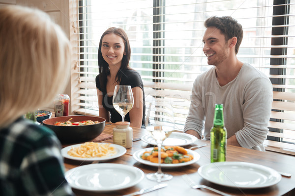 Cheerful young people enjoying meal while sitting at the dinning table Stock photo © deandrobot