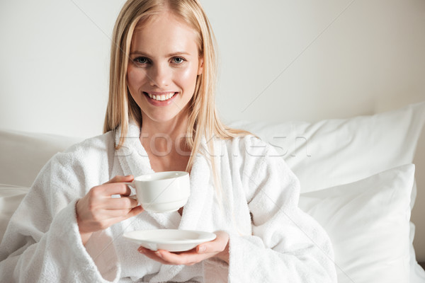 Happy smiling woman in bathrobe holding cup of coffee Stock photo © deandrobot