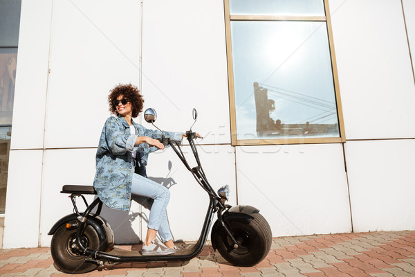 Happy curly woman sitting on a modern motorbike Stock photo © deandrobot