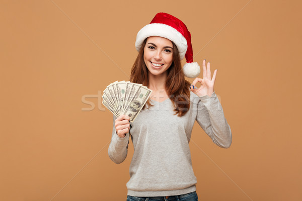 Cheerful caucasian lady wearing christmas hat showing okay gesture Stock photo © deandrobot
