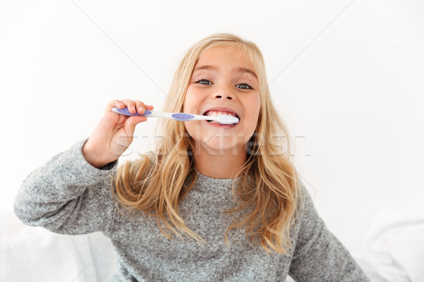 Close-up portrait of cute kid in gray pajamas brushing her teeth Stock photo © deandrobot