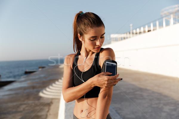 Mosolyog fiatal sportok nő hallgat zene Stock fotó © deandrobot