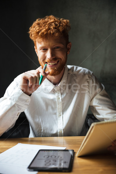 Close-up portrait of young happy readhead curly man, sitting at  Stock photo © deandrobot