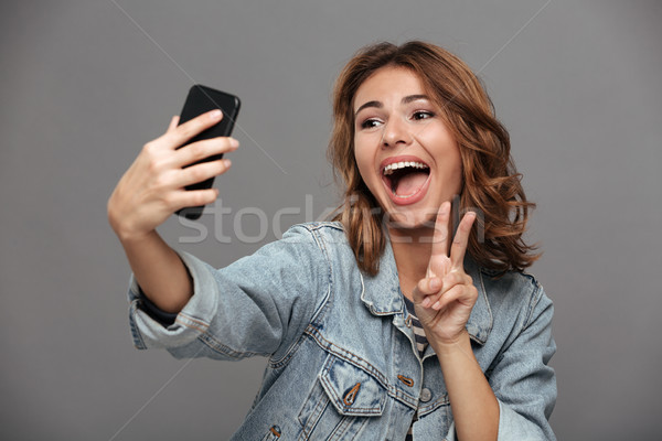 Close-up photo of overjoyed brunette teen girl showing peace ges Stock photo © deandrobot