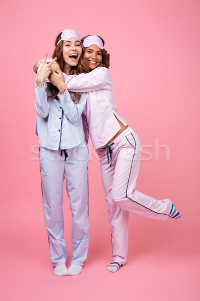 Cheerful two girls friends in pajamas isolated over pink background Stock photo © deandrobot