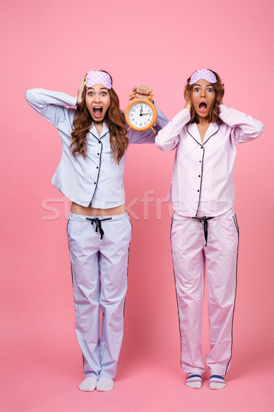 Two shocked confused screaming friends women holding alarm Stock photo © deandrobot