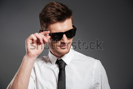 Portrait of a serious man in earphones and sunglasses Stock photo © deandrobot