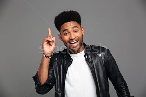 Cheerful afro american stylish man pointing with finger upward,  Stock photo © deandrobot