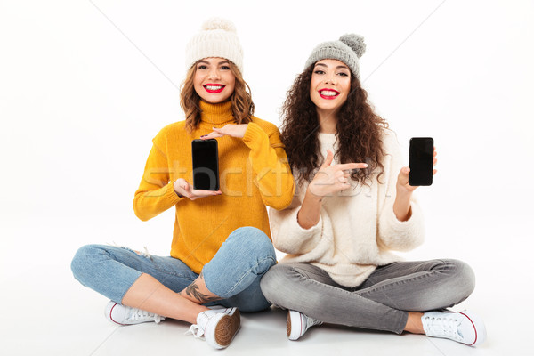 Two happy girls in sweaters and hats sitting on floor Stock photo © deandrobot