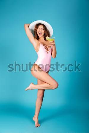 Full length portrait of a smiling girl dressed in swimsuit Stock photo © deandrobot