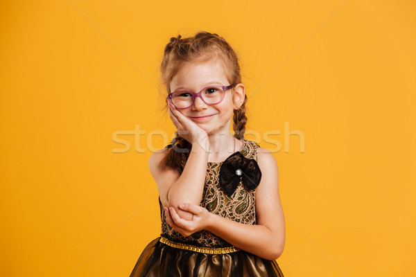 Smiling girl child standing isolated over yellow background Stock photo © deandrobot