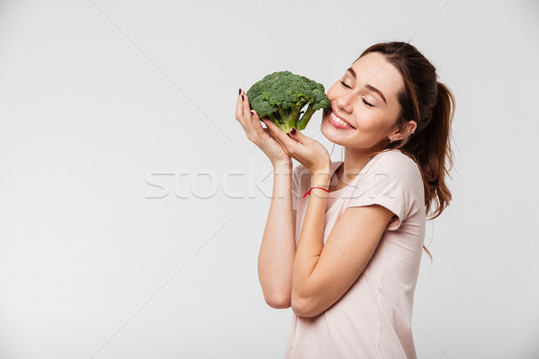 Portrait of a satisfied pretty girl holding broccoli Stock photo © deandrobot