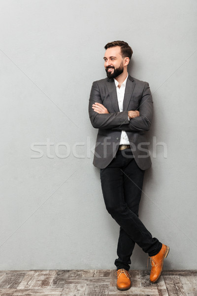Full-length portrait of young man in jacket posing on camera wit Stock photo © deandrobot