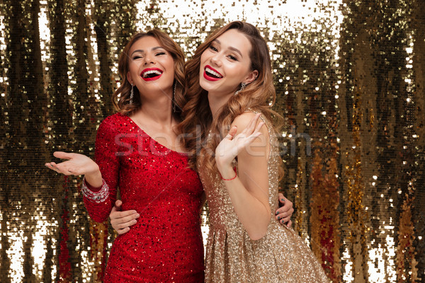 Portrait of two happy young women in sparkly dresses Stock photo © deandrobot