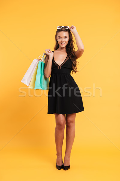 Smiling young lady in black dress holding shopping bags. Stock photo © deandrobot