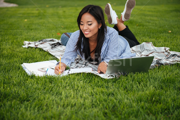 Beautiful asian female student, taking notes, lying on checkered Stock photo © deandrobot