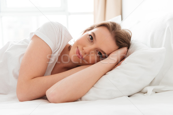 Cheerful young woman lies in bed at morning looking camera. Stock photo © deandrobot